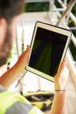 Byggnadsarbetare Using Digital Tablet på byggnadsplats Arkivbilder