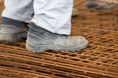 Byggnadsarbetareanseende på förstärkningingrepp Fotografering för Bildbyråer