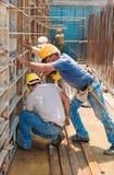 Byggnadsarbetarear som är upptagna med formworkramar Arkivbilder