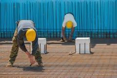 Byggnadsarbetarear som binder in stålstänger med trådar Royaltyfri Bild