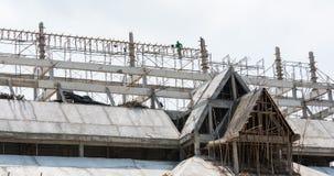 Byggnadsarbetarearbete på att inrama en byggnad Arkivfoto