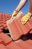 Byggnadsarbetaren belägger med tegel att taklägga reparerar royaltyfri bild