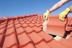 Byggnadsarbetaren belägger med tegel att taklägga reparerar huset Fotografering för Bildbyråer
