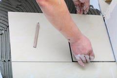 Byggnadsarbetaren belägger med tegel hemma, bindemedel för tegelplattagolvet arkivfoto