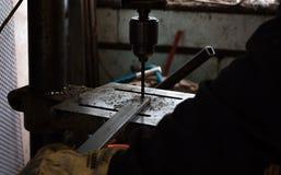 Byggnadsarbetaren borrar hålet i stång av metalljärn genom att använda den industriella drillborren Royaltyfri Fotografi