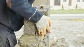 Byggnadsarbetaren bygger tegelstenväggen, closeupsikt på konstruktionsplatsen royaltyfri foto