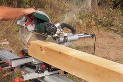 Byggnadsarbetaren Cutting Beam med såg Arbetare som klipper timmerträ med chainsawen Sågsawingtimmer arkivfoton