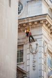 Byggnadsarbetaren fäller sig ned in i position för att utföra strömförsörjningen Fotografering för Bildbyråer