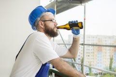 Byggnadsarbetaren i arbetskläder, skyddande handskar och en hjälm på huvudet dricker öl från flaskan Arbete på hög höjd Arkivfoto