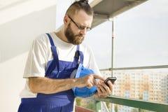 Byggnadsarbetaren i en arbetsdress rymmer ett konstruktionshjälm-, mobiltelefon- och visartavlanummer i hand Arbete på hög höjd S Royaltyfri Fotografi
