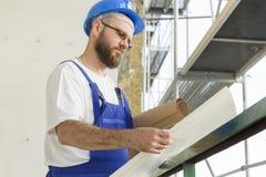 Byggnadsarbetaren i en arbetsdress rymmer ett konstruktionshjälm-, mobiltelefon- och visartavlanummer i hand Arbete på hög höjd S Royaltyfri Foto