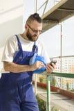 Byggnadsarbetaren i en arbetsdress rymmer ett konstruktionshjälm-, mobiltelefon- och visartavlanummer i hand Arbete på hög höjd S Royaltyfri Bild
