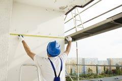 Byggnadsarbetaren i en skyddande hjälm- och arbetsdress mäter materialet till byggnadsställning på en konstruktionsplats Royaltyfri Foto