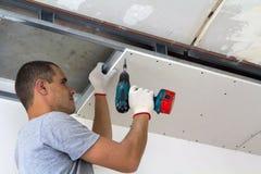 Byggnadsarbetaren monterar ett inställt tak med den drywallen royaltyfri foto