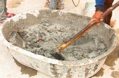 Byggnadsarbetaren under att använda hoen till blandningen blöter cementerar Arkivbilder