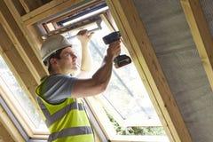 Byggnadsarbetaren Using Drill To installerar fönstret Arkivfoton