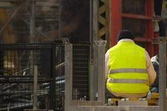 Byggnadsarbetaren vilar på rekonstruktionområdet Arkivfoton