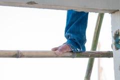 Byggnadsarbetares fot som beträder på ett bambumaterial till byggnadsställning royaltyfri bild