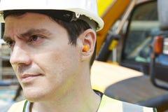 ByggnadsarbetareWearing Protective Ear proppar royaltyfri bild