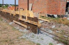 Byggnadsbetonggrund med tjock skiva och järnstång för nytt staket royaltyfri foto