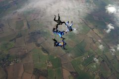 byggnadsbildande fyra skydivers royaltyfri foto
