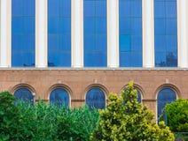 Byggnadsfasad med blått exponeringsglas med träd i förgrunden arkivbild