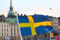 Byggnadsfasad med svenskflaggan Arkivbild