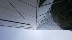 Byggnadsfasadhud uppåt som gör klar blå himmel Arkivfoton