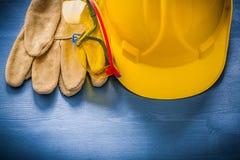 Byggnadshjälmen rullar med ögonen säkerhetshandskar på träbrädeconstructi Royaltyfri Fotografi