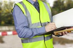 Byggnadsinspektör med anmärkningar för spritnivåhandstil i hans mapp Arkivbilder