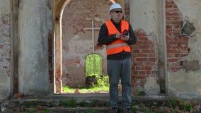 Byggnadsinspektör som använder minnestavlaPC på den gamla kyrkan för återställande arkivfilmer