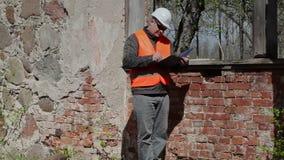 Byggnadsinspektör som skriver nära fönster stock video
