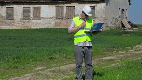 Byggnadsinspektör som skriver nära gammalt övergett skadat hus på gräsfält arkivfilmer