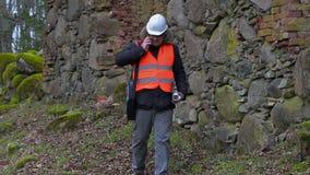 Byggnadsinspektören med den smarta telefonen och dokumentation på gammalt fördärvar arkivfilmer