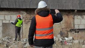 Byggnadsinspektörer med minnestavlaPC och dokumentation stock video