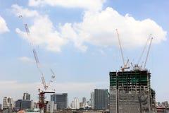 Byggnadskonstruktionsplats med kranar mot blå himmel, konstruktion arkivfoton