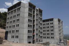 Byggnadskonstruktionsplatsen under en blå himmel, grå färg hårdnar Royaltyfria Bilder