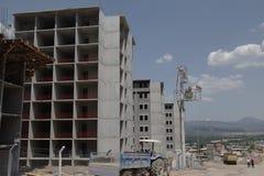 Byggnadskonstruktionsplatsen under en blå himmel, grå färg hårdnar Arkivbilder