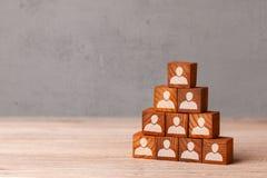 Byggnadslag Ledaren bygger pyramiden från kuber med anställda Rekryteringbegrepp kopiera avstånd royaltyfri foto