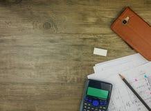 Byggnadsplan, brevpapper och räknemaskin för bästa sikt på grå träbakgrund Arkivbild