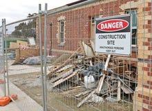Byggnadsplats under konstruktion med varningstecknet och högar av spillror Arkivbild