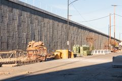 Byggnadsställningområde av vägkonstruktionsmaterial bredvid en konkret behållande vägg och en högstämd huvudväg Fotografering för Bildbyråer