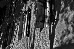 Byggnadsvägg med svarta fönsterslutare Arkivbild