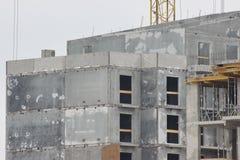Byggnationer av moderna låghus- bostads- byggnader konstruktionsplats på huset kranar special utrustning arkivbilder