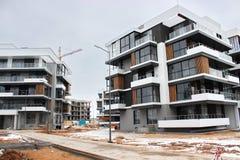 Byggnationer av moderna låghus- bostads- byggnader konstruktionsplats på huset kranar special utrustning royaltyfri fotografi