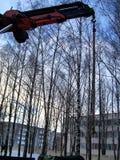 Byggnationer bilpåfyllning-lyftande kranen, lastbilkranpil mot bakgrunden av träd, vinter, staden, arkivfoton