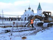 byggnationer grävskopan på larven till kursen, reparation av rör av uppvärmning i staden, kostar den geodezichesy bäraren royaltyfri bild