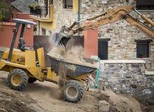 Byggnationer med en grävskopa och en mini- dumper Arkivbilder