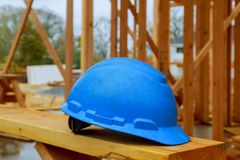 Byggnationsäkerhetshjälmar för yrkesmässiga byggmästare förläggas på träbräden Säkerhetshjälmar för industriarbetarekläder arkivfoto