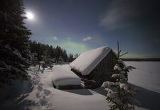 Byhus i ljusen av månen och norrsken Arkivbilder